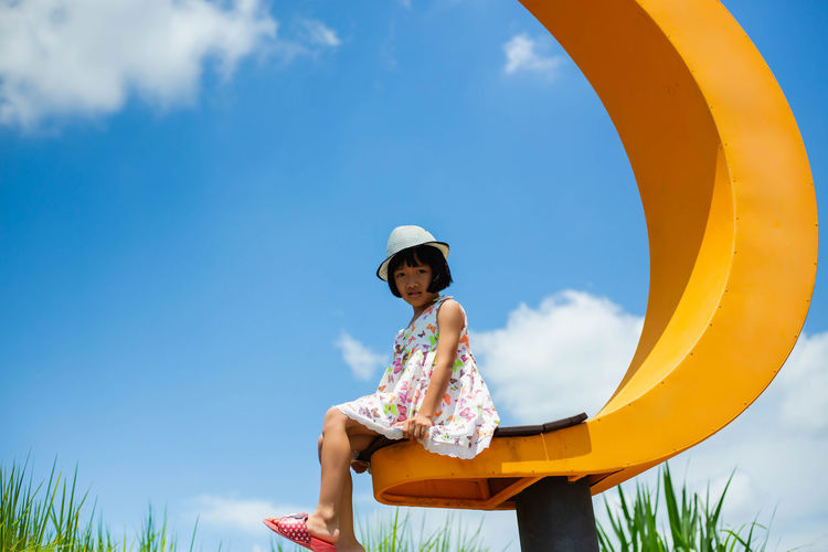 Low angle view of girl sitting against sky
