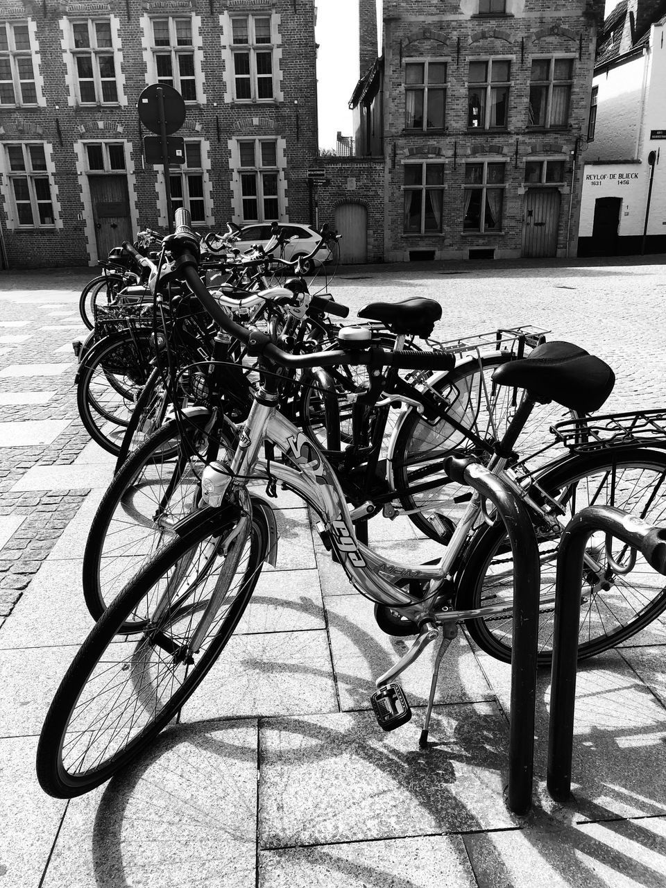 architecture, bicycle, city, building exterior, built structure, land vehicle, transportation, mode of transportation, street, building, stationary, day, parking, no people, outdoors, sidewalk, footpath, nature, city life, shadow, wheel