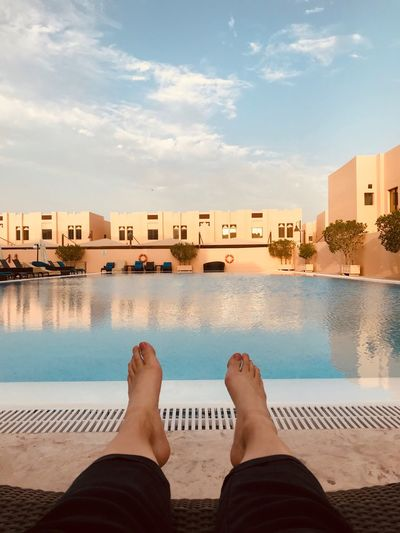 Arabian Moment EyeEm Selects Low Section Human Leg Water Body Part Personal Perspective Human Body Part Swimming Pool Nature Cloud - Sky barefoot Building Exterior Human Foot Real People Architecture Sky Built Structure Lifestyles Leisure Activity One Person Outdoors