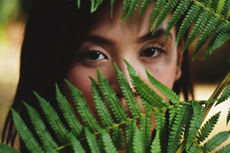 Close-up portrait of young woman looking through plants