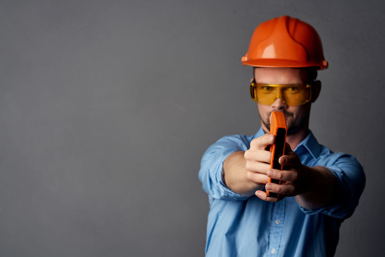 Midsection of man holding glass against colored background