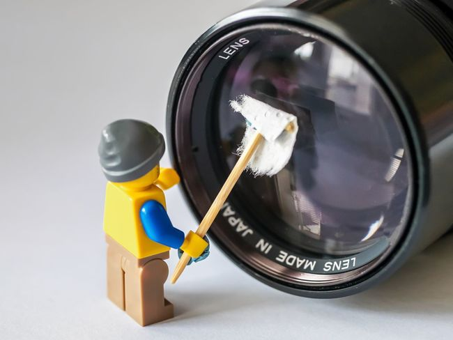 Small plastic figure cleaning a photo lens Cleaning Figure Fun Funny Work Working Clean Close-up Cloth Day Indoors  Lens No People Photo Lens Plastic Stick Studio Shot White Background