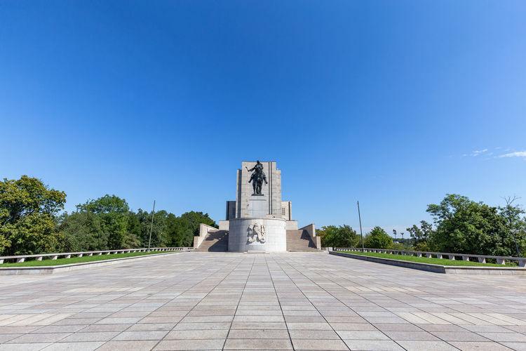 Temple against building against clear blue sky