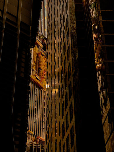 Low angle view of illuminated lights hanging in building at night