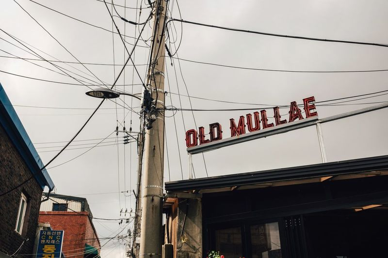 Old Mullae Lifestyles Mullae Wires In The Sky Western Script Sign Messy South Korea Old Street Korea Seoul Cable Text Architecture Built Structure Power Line  Building Exterior Low Angle View Outdoors No People Sky