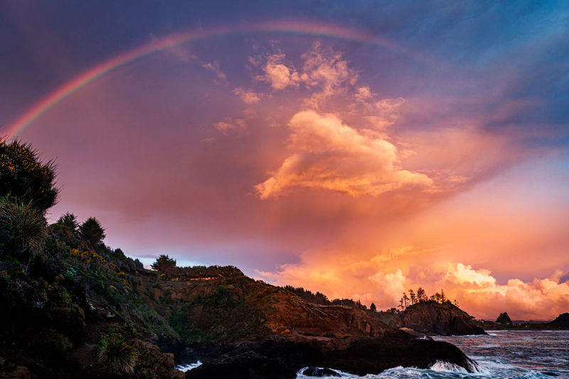 Scenic view of rainbow over sea against sky during sunset