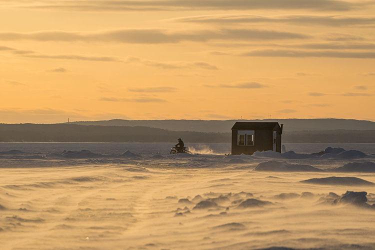 Motocrosso on frozen lake against sky during sunset