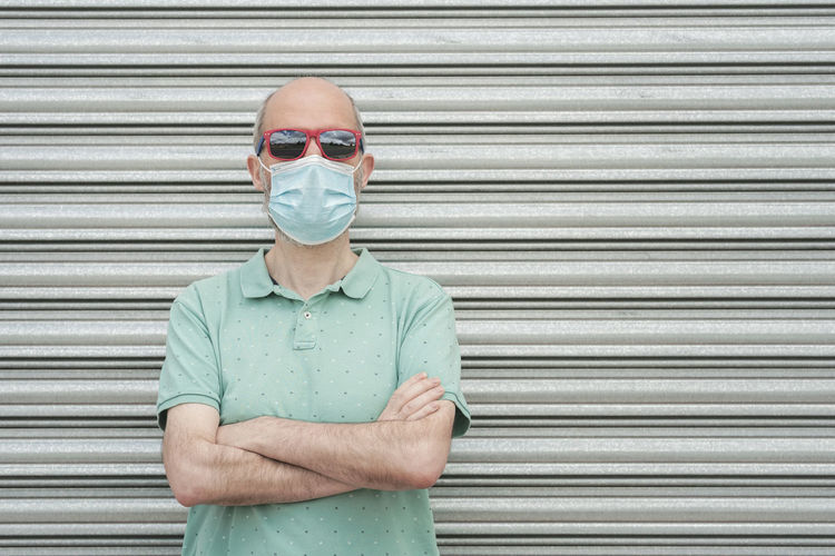 Portrait of man wearing mask standing against shutter