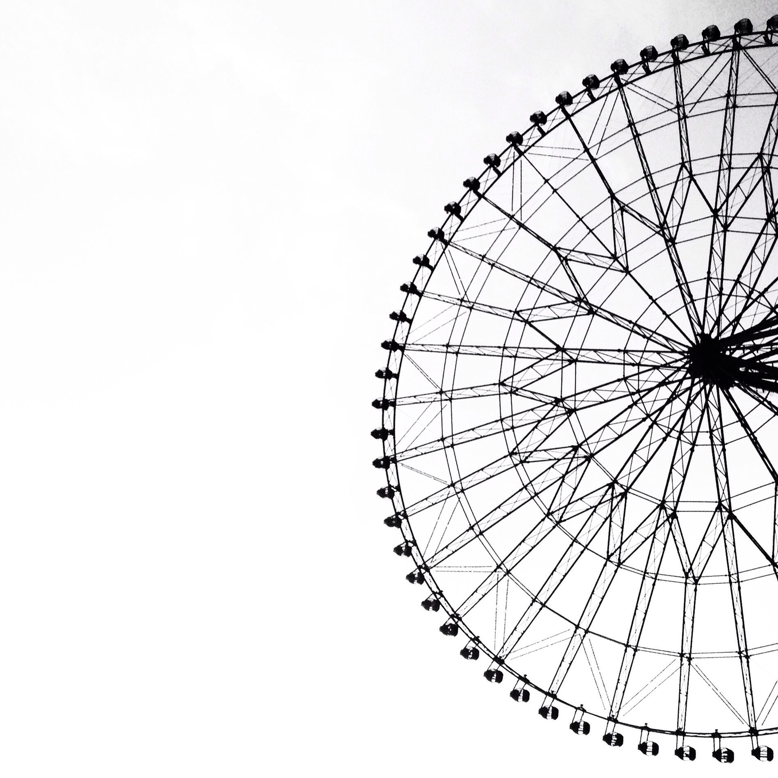low angle view, ferris wheel, amusement park, amusement park ride, arts culture and entertainment, clear sky, sky, copy space, circle, built structure, outdoors, day, no people, pattern, metal, big wheel, large, architecture, silhouette, part of