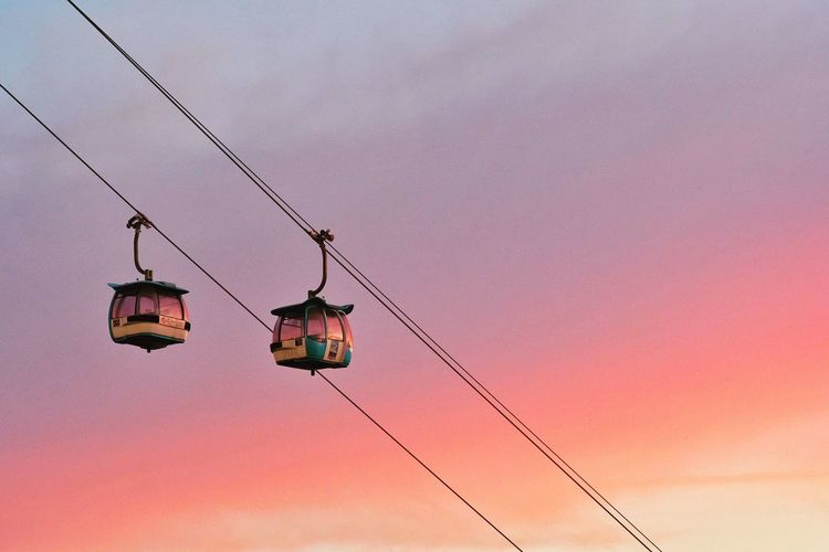 Low angle view of overhead cable car against sky during sunset