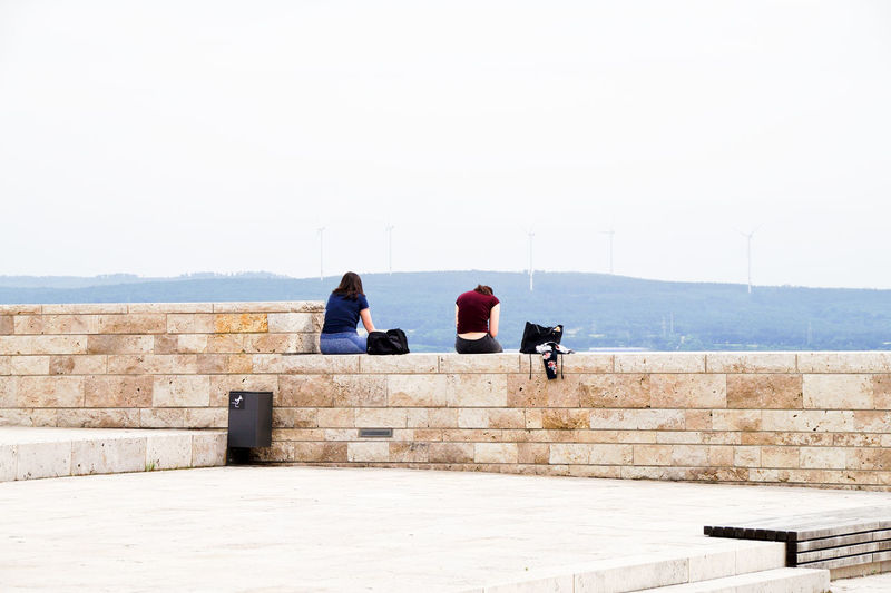 Rear view of people sitting on wall against sky