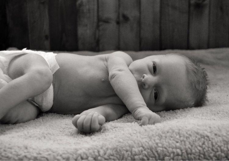 Portrait of innocent new born baby boy lying on bed