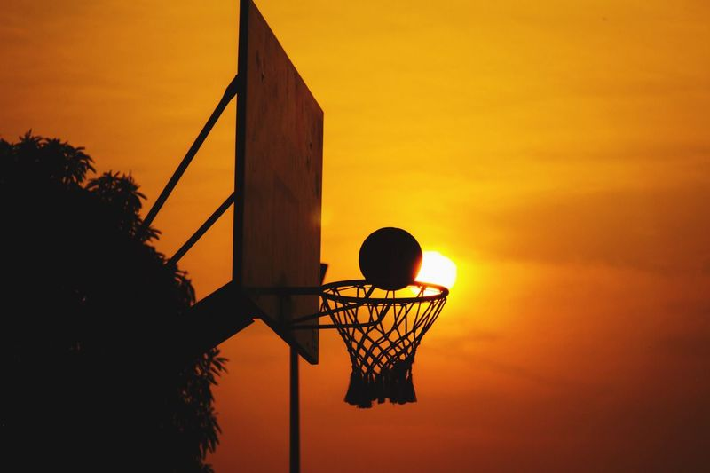 Low angle view of basketball hoop against orange sky