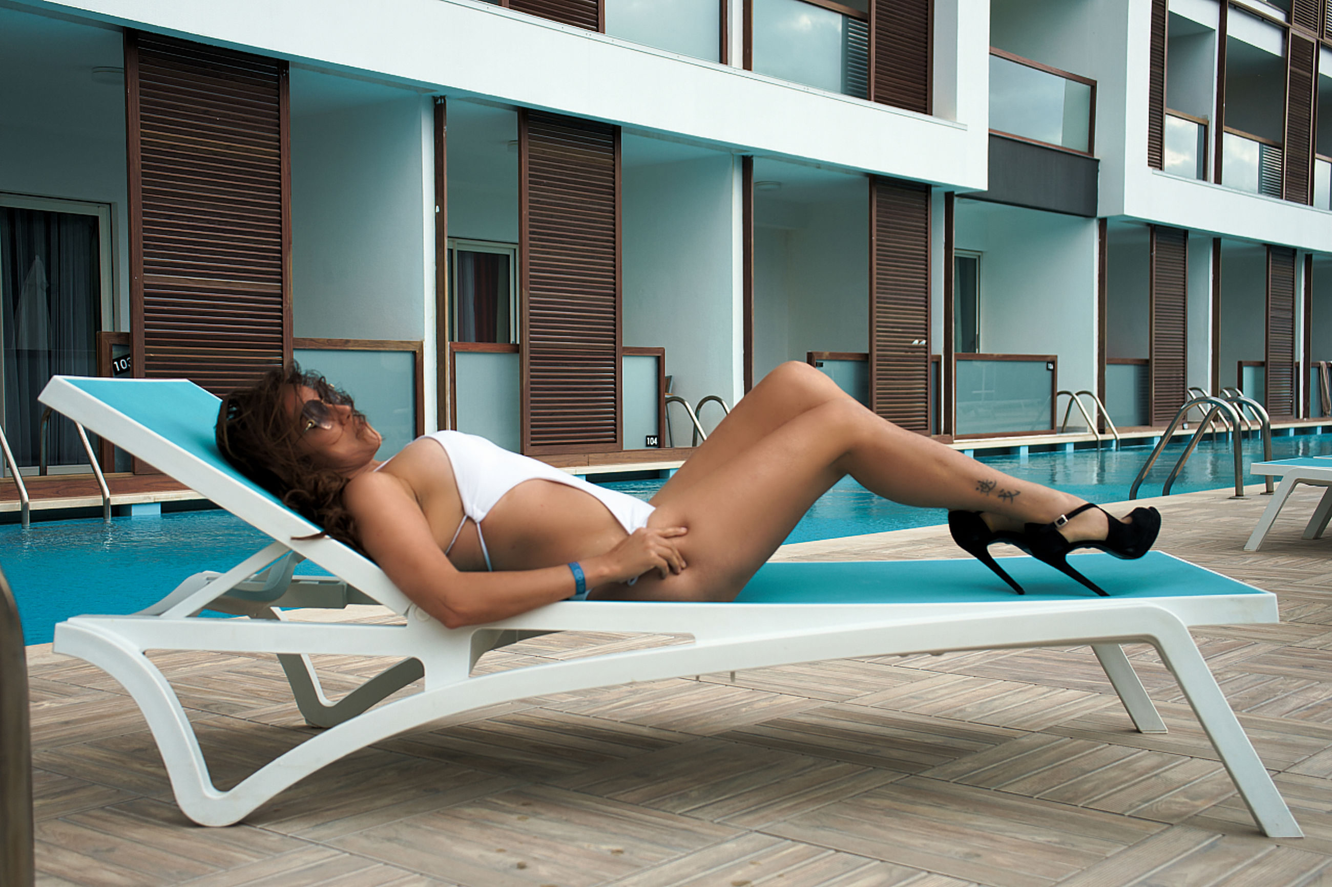 sitting, adult, relaxation, young adult, one person, lifestyles, women, lying down, full length, architecture, wellbeing, limb, clothing, building exterior, summer, swimming pool, human leg, leisure activity, furniture, built structure, female, chair, exercising, sun tanning, swimwear, resting, comfortable, seat, side view, nature, sun, day, outdoors, sunbathing, bikini, city, building, chaise longue, window