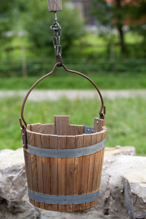 Wooden bucket of an antique draw well Farm Retro Absence Bucket Close-up Container Draw Well Extraction Focus On Foreground Garden Groundwater Hanging Medieval Metal Nature No People Outdoors Plant Rural Scene Selective Focus Tree Water Well  Wood - Material