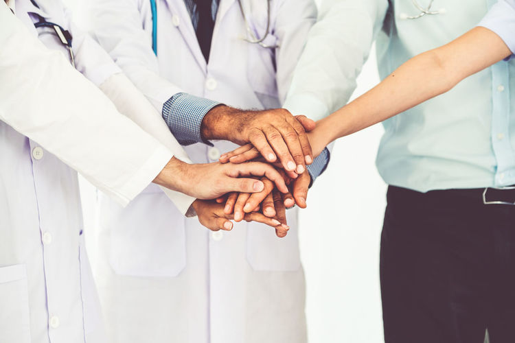 Midsection of doctors stacking hands