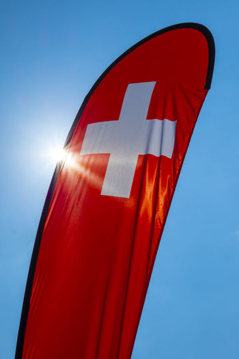 Swiss Banner Flag with Sunlight and Against Blue Sky in Switzerland. Red Blue Sky Clear Sky Sunlight No People Day Sunny Flag Outdoors Sun Business Wind Close-up Patriotism Communication Swiss Flag Banner Cross Identity Patriotism Colorful Simplicity Nationalism White Color