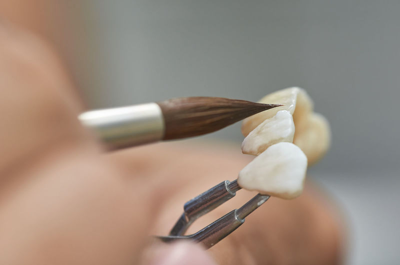 Close-up of hand painting artificial teeth