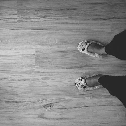 Low section of woman standing on hardwood floor at home