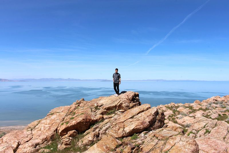Full length of mid adult man standing on rock by sea against sky