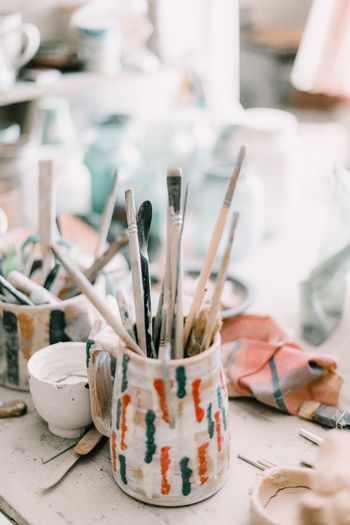 Close-Up Of Paintbrushes In Container On Table