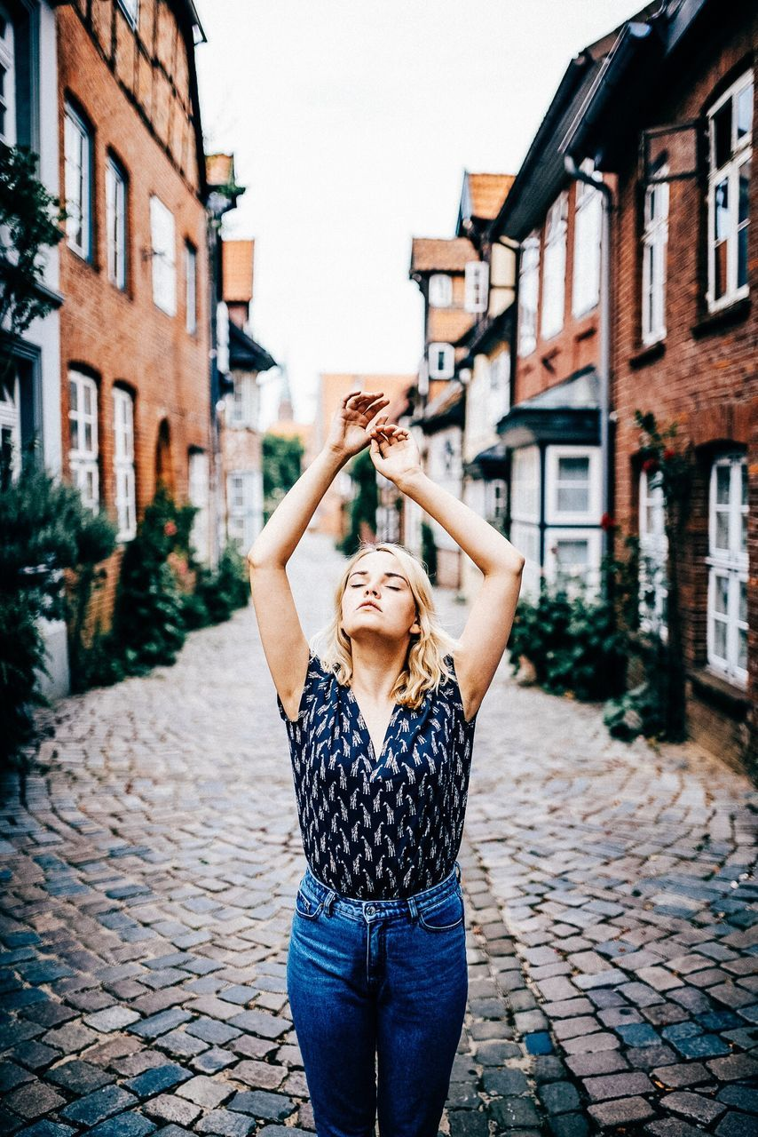 Young Woman With Eyes Closed And Arms Raised Standing On Footpath Amidst Buildings