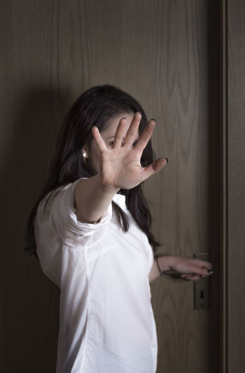 Woman showing stop gesture while standing by door