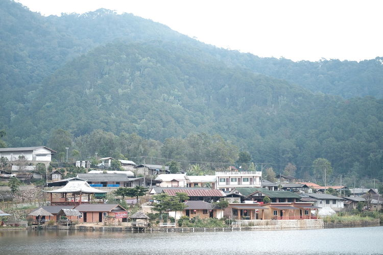 Houses by river against mountain