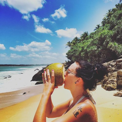Side view of woman drinking coconut water at beach against sky