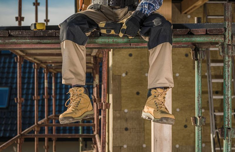 Low section of worker sitting at construction site
