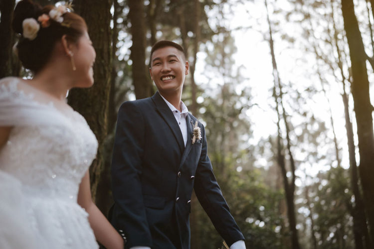 The newlyweds happy in the atmosphere of the pine forest, looking and feeling warm.