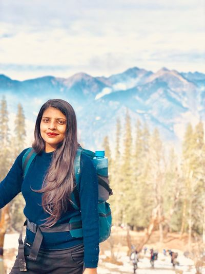 Portrait of smiling young woman standing on mountain during winter
