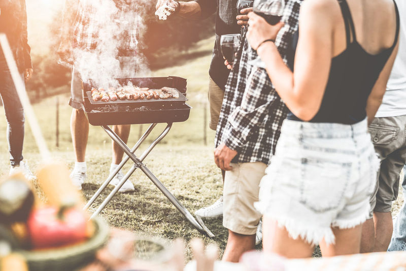 Young friends making barbecue outdoor Food And Drink Food Barbecue Men Real People Leisure Activity Lifestyles Barbecue Grill Smoke - Physical Structure Adult Preparation  People Day Outdoors Preparing Food