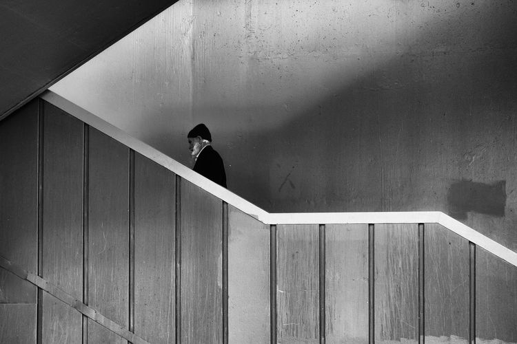 Side view of man walking on steps in building