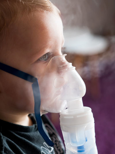 Small caucasian kid inhaling at home with oxygen mask Child Childhood Inhalation Kid Inhaler Medical Asthma Home Medicine Boy Health Allergy Asthmatic Care Respiratory Patient Treatment Young Sick Disease Illness Breathing Oxygen Mask Little Caucasian Face Therapy Airplane Flu Inhaling Medication Allergic Innocence Close-up