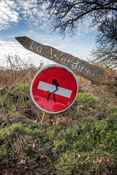 ZAD Notre Dame Des Landes Circle Clock Clock Face Communication Day Grass Guidance Minute Hand Nature No People Outdoors Red Road Sign Sky Time Tree