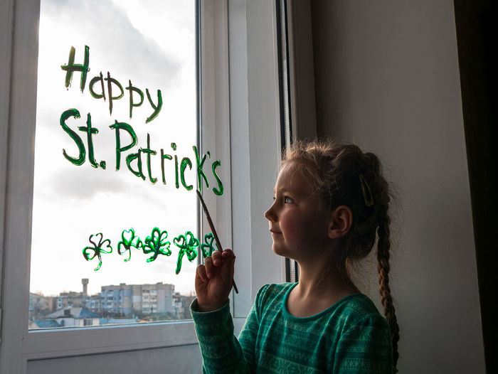 Drawing st. patrick's day child paints green three-leaved shamrock draws clover on window. stay home