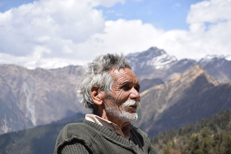 Senior Man Standing Against Mountain