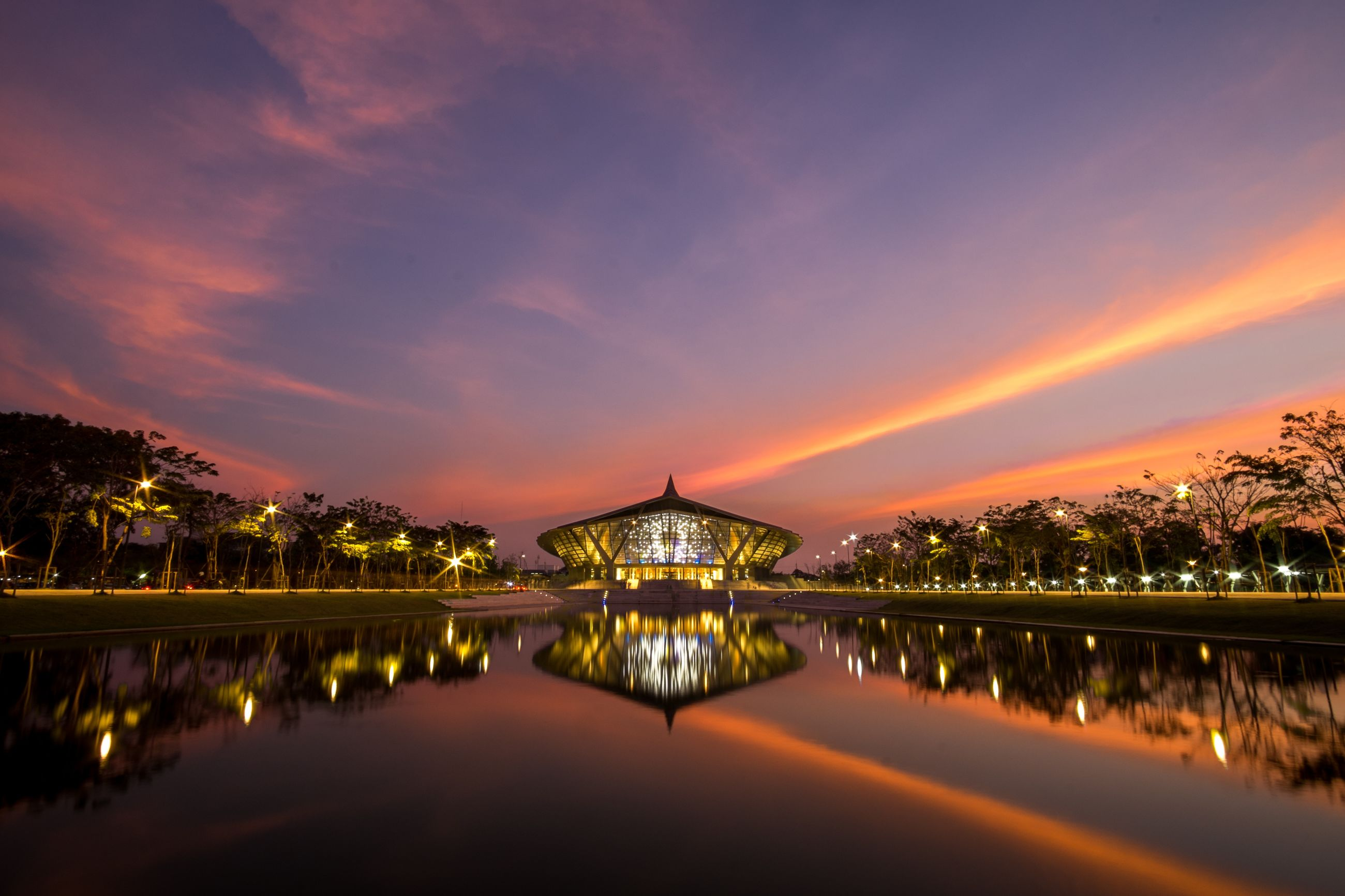 reflection, dusk, city, night, architecture, illuminated, sunset, water, building exterior, cityscape, sky, bridge - man made structure, travel destinations, cloud - sky, business finance and industry, waterfront, outdoors, built structure, multi colored, nature, landscape, vacations, no people, scenics, urban skyline, tree