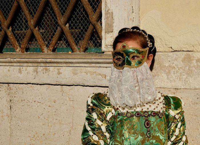 Mature woman wearing costume against wall during venice carnival
