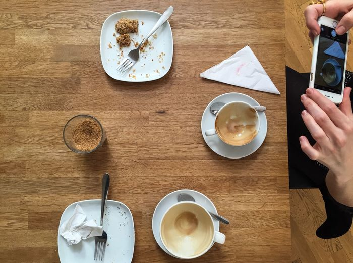Midsection of woman photographing empty coffee cup while sitting at table