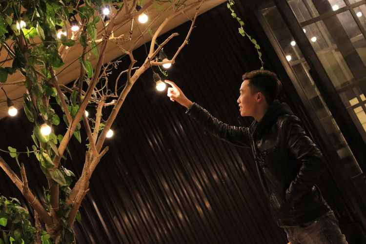 Young man touching electric bulb hanging from tree