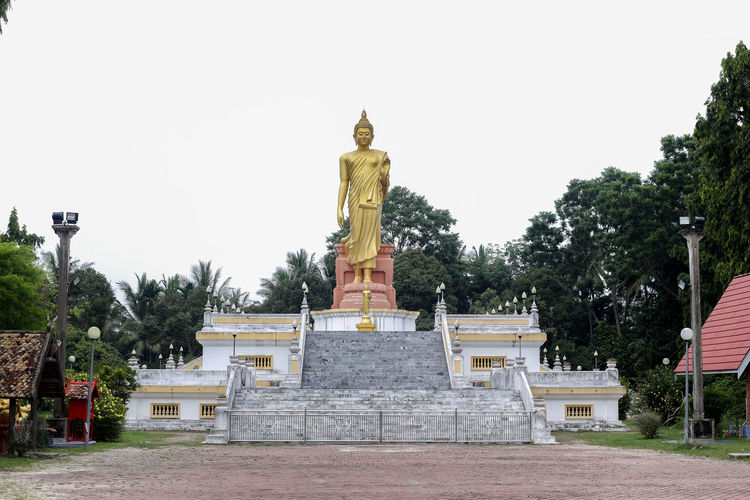 Wat Pikulthong Standing Buddha in Tumpat, Kelantan Budhism Budhist Temple Buddhist Temple Sculpture Statue Art And Craft Representation Human Representation Tree Architecture Religion Male Likeness Belief Plant Spirituality Built Structure Sky Creativity Place Of Worship Nature No People Idol