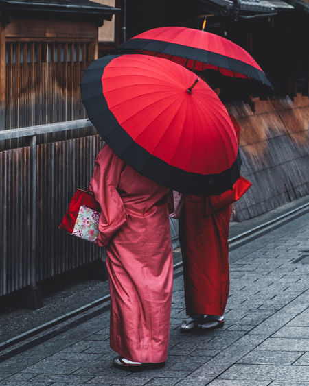 Rear view of red umbrella walking on street