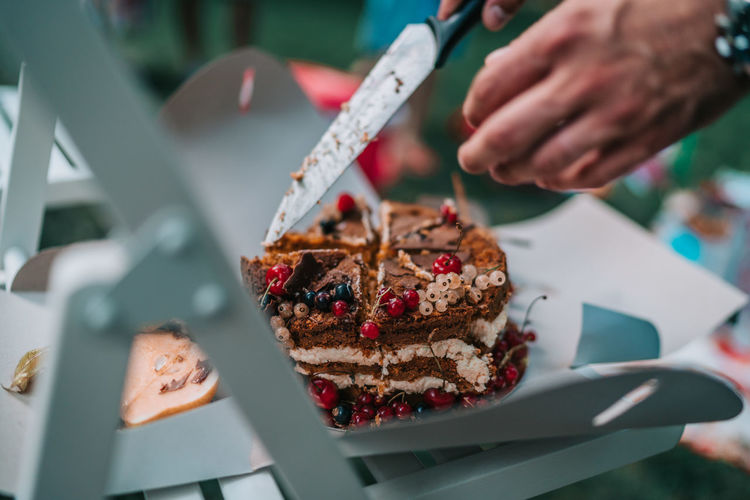 Cropped image of hands cutting cake