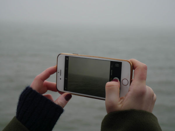 A sea through a screen. Adult Adults Only Close-up Communication Connection Day Device Screen Digital Viewfinder Gray Background Holding Human Hand IPhone Liquid-crystal Display Mobile Phone Mobilephotography One Person Outdoors People Photography Portability Portable Information Device Smart Phone Technology Touch Screen Wireless Technology