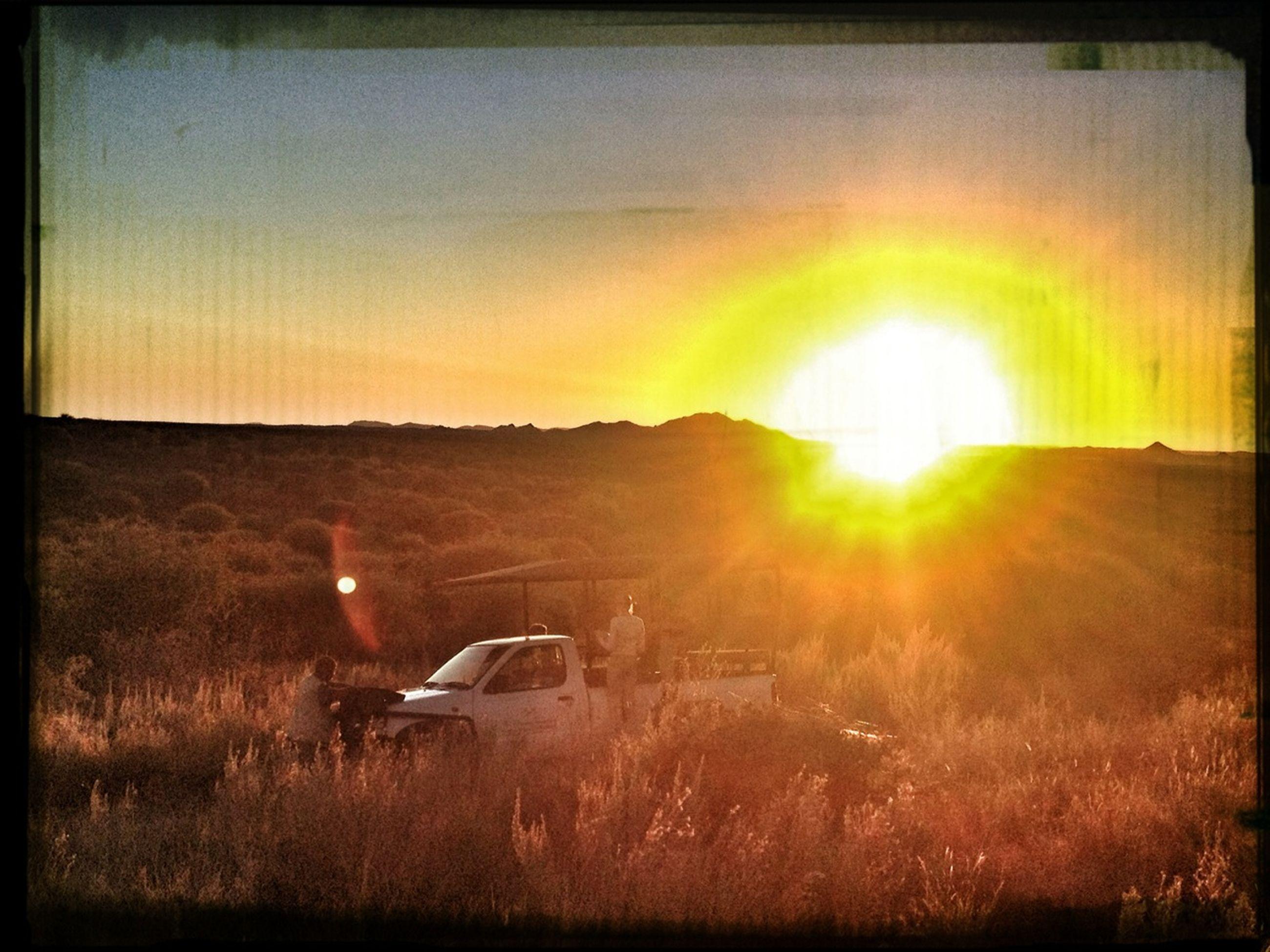 transfer print, sunset, sun, auto post production filter, field, landscape, grass, sunlight, sky, transportation, orange color, lens flare, sunbeam, nature, rural scene, mode of transport, tranquil scene, scenics, tranquility, outdoors