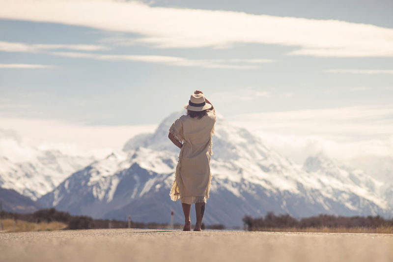 A boho hippy lady in white dress with hat stands in the middle of road with aoraki snow mountain in background Travel Photography Beauty In Nature Cloud - Sky Cold Temperature Day Environment Full Length Hippy Landscape Leisure Activity Lifestyles Mountain Mountain Range Nature One Person Outdoors Real People Roadtrip Scenics - Nature Sky Standing Tranquil Scene Tranquility Travel Destinations Warm Clothing