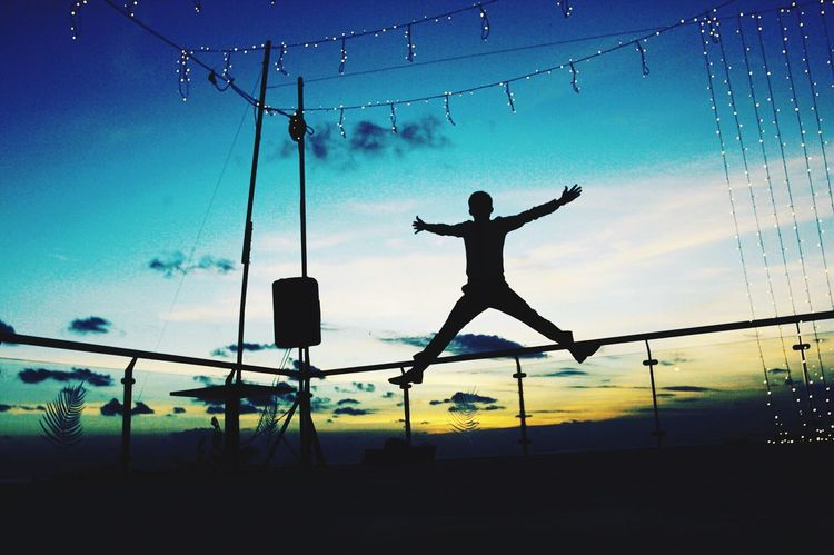 Silhouette Full Length Leisure Activity Motion Jump Dusk Blue Scenics Enjoyment Sky Mid-air Fun Outdoors Carefree Focus On Foreground Tranquil Scene Nature Cloud - Sky Beauty In Nature