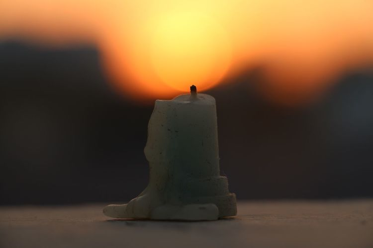 Close-up of wax candle against orange sky during sunset